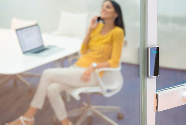 Mujer con camisa amarilla y pantalón blanco, sentada en una silla blanca, hablando por teléfono y en la puerta de entrada, hay un lector NÜO surf, lector de control de acceso de la marca NÜO