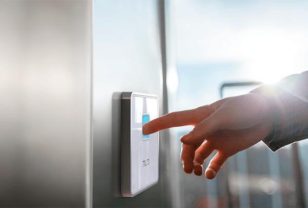mano colocando dedo sobre lector de huella NÜO Awa de color blanco, para ingresar a una puerta controlada por un sistema de control de acceso